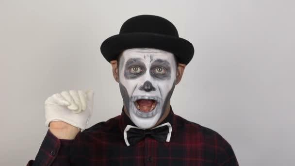 Hrozný muž v maskérně mává rukou, aby se rozloučil se svou obětí. Děsivý klaun se podívá do kamery a hrozně se zasměje. Děsivé grimasy klauna, který se dívá do kamery. Halloween kostým.