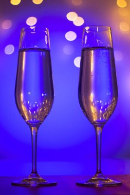 Champagne sparkling wine glasses of prosecco cava in nightclub party bar during wedding in Ibiza Spain with lights behind.
