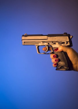 Woman's hand holding automatic pistol gun.