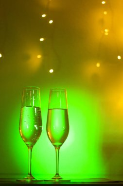 Champagne sparkling wine glass of prosecco cava in discotque party bar during wedding in Ibiza Spain with lights behind.