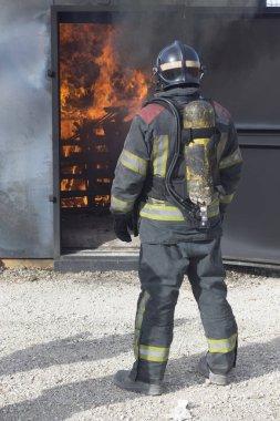İtfaiyeci yangın söndürme istasyonunu söndürüyor. Acil durum güvenlik tatbikatı prosedürü..
