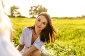 glückliche junge Frau blickt in die Kamera, während sie auf der grünen Wiese sitzt
