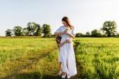 schöne Mutter mit Blumenstrauß und Tochter umarmen sich in der grünen Wiese bei Sonnenuntergang