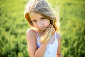 Photo close-up portrait of cute little child in white dress posing in green field and looking at camera