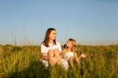 Fotografie Mutter und Tochter auf dem grünen Rasen auf Sonnenuntergang sitzen und plaudern
