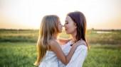 Detailní portrét matka a dcera objímat a dotýká nosy v zelené oblasti na západ slunce