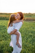 Fotografie mother and daughter embracing in green field on sunset
