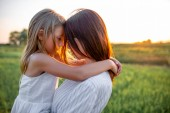 Nahaufnahme Porträt von Mutter und Tochter, die sich bei Sonnenuntergang auf der grünen Wiese umarmen