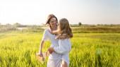 schöne glückliche Mutter und Tochter umarmen sich im grünen Feld bei Sonnenuntergang