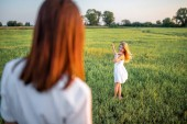 Mutter und glückliche Tochter verbringen Zeit miteinander auf der grünen Wiese