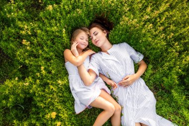 Top view of mother and daughter relaxing while lying in flowery meadow stock vector