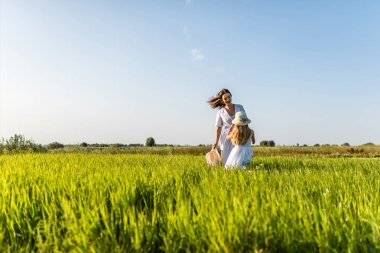 beautiful smiling mother and daughter playing in green meadow