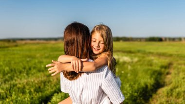 mother embracing with her happy daughter in green meadow