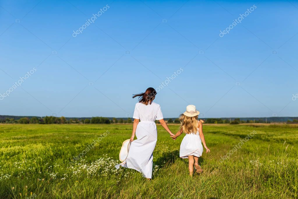 rear view of mother and daughter walking together by green field on sunny day