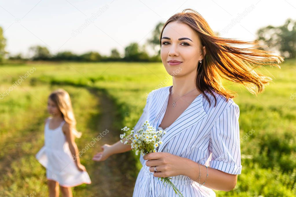 beautiful young mother with field flowers bouquet and little daughter blurred on background in green field