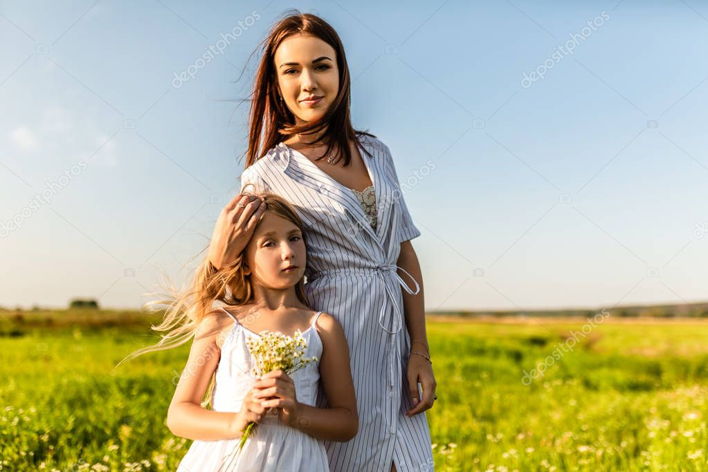 mother and daughter in white dresses looking at camera together in green field