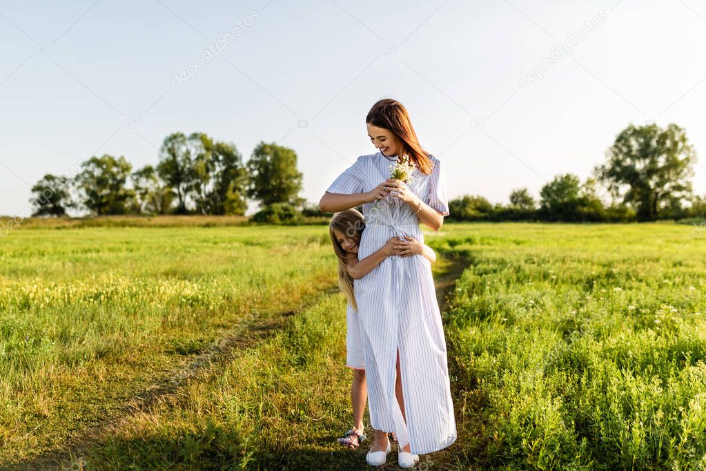 beautiful mother with bouquet and daughter embracing in green meadow on sunset
