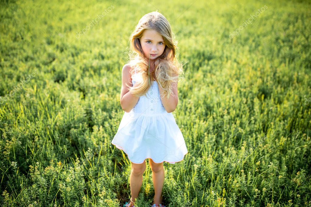 cute little child in white dress posing in green field and looking at camera