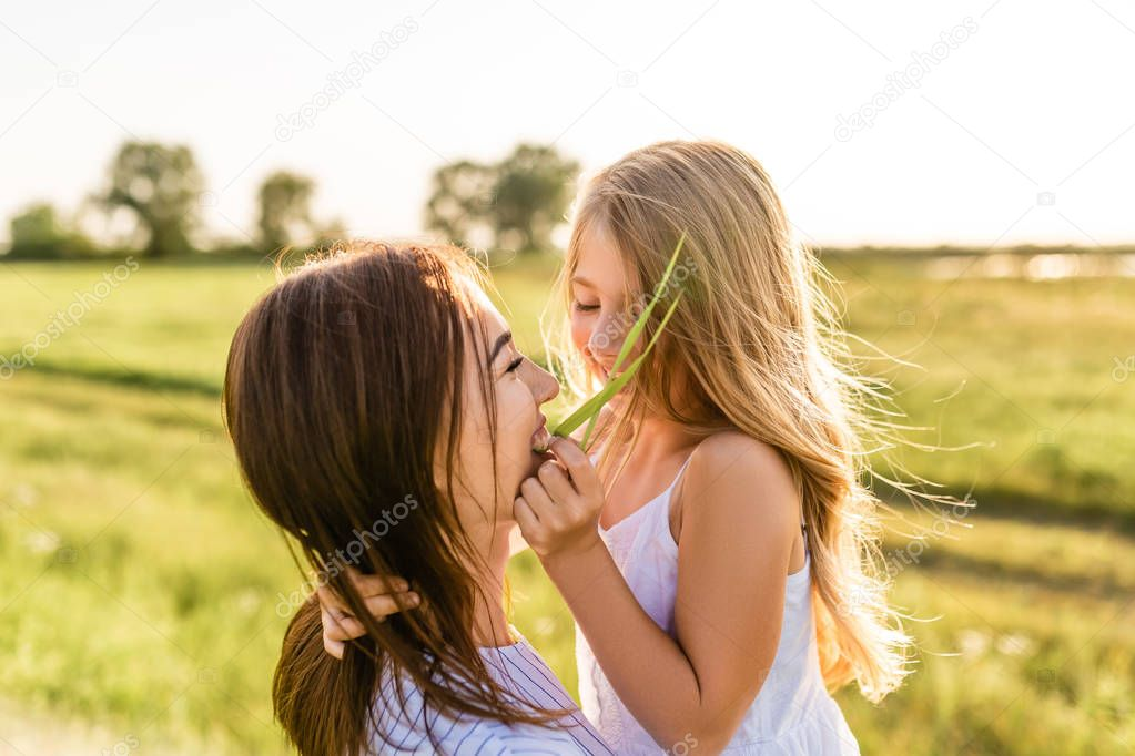 close-up portrait of mother and daughter having fun together in green meadow