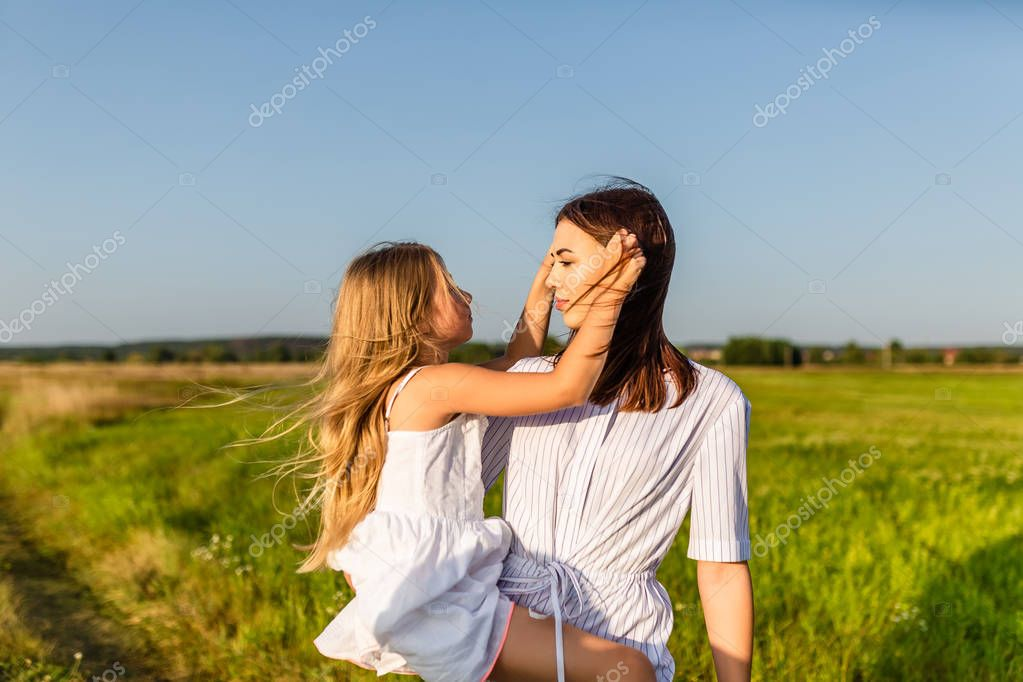 loving mother and daughter standing in green meadow