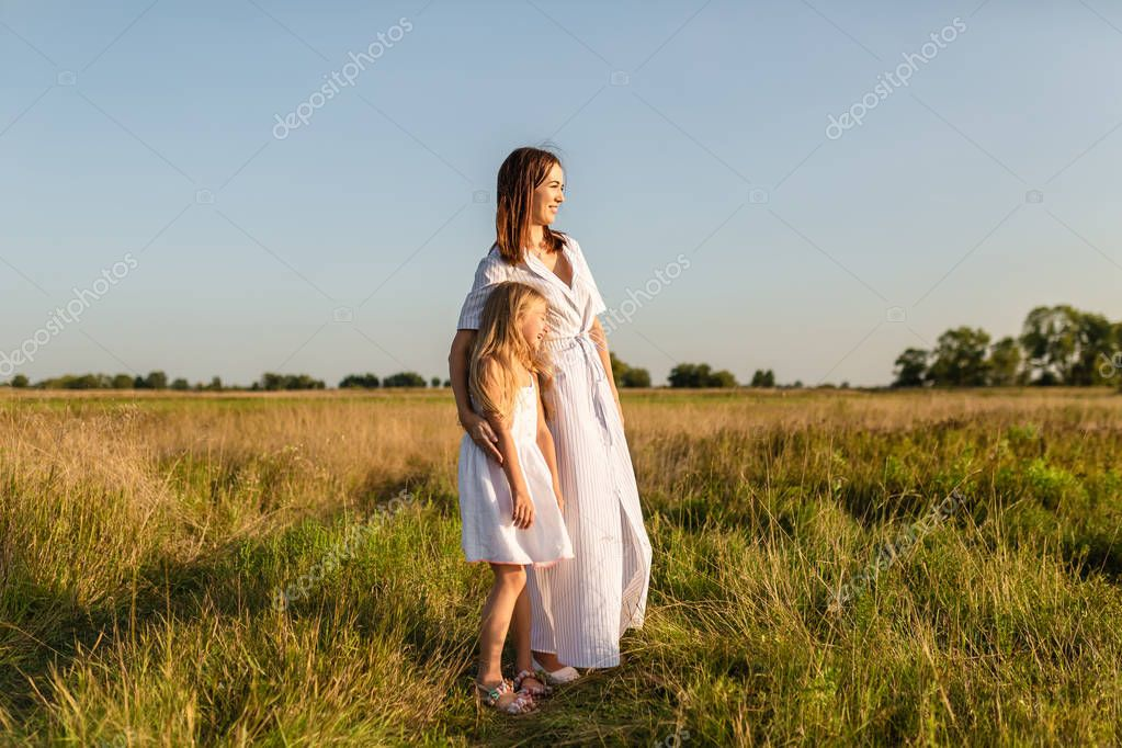 mother and daughter standing in field and looking at sunset