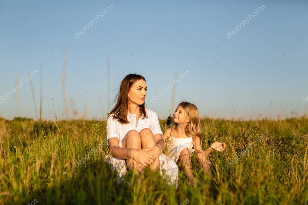 mother and daughter sitting on green grass on sunset and chatting
