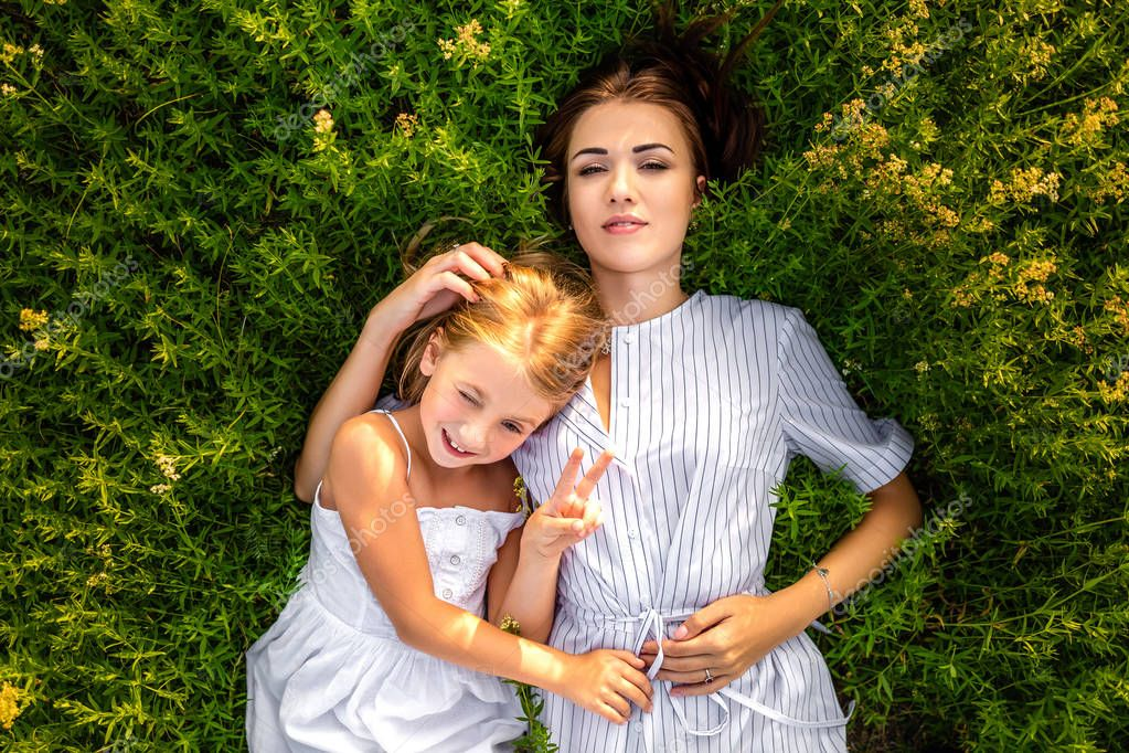 top view of mother and daughter lying in flowery meadow and looking at camera