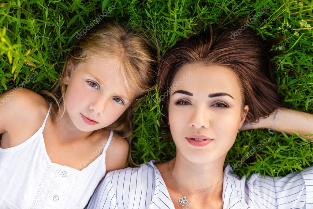 top view of mother and daughter lying on green grass and looking at camera