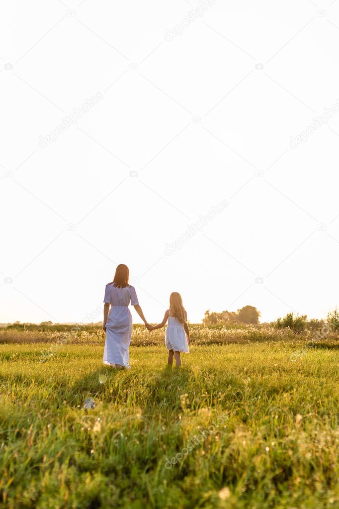rear view of mother and daughter holding hands and walking by green meadow with sunset sky on background