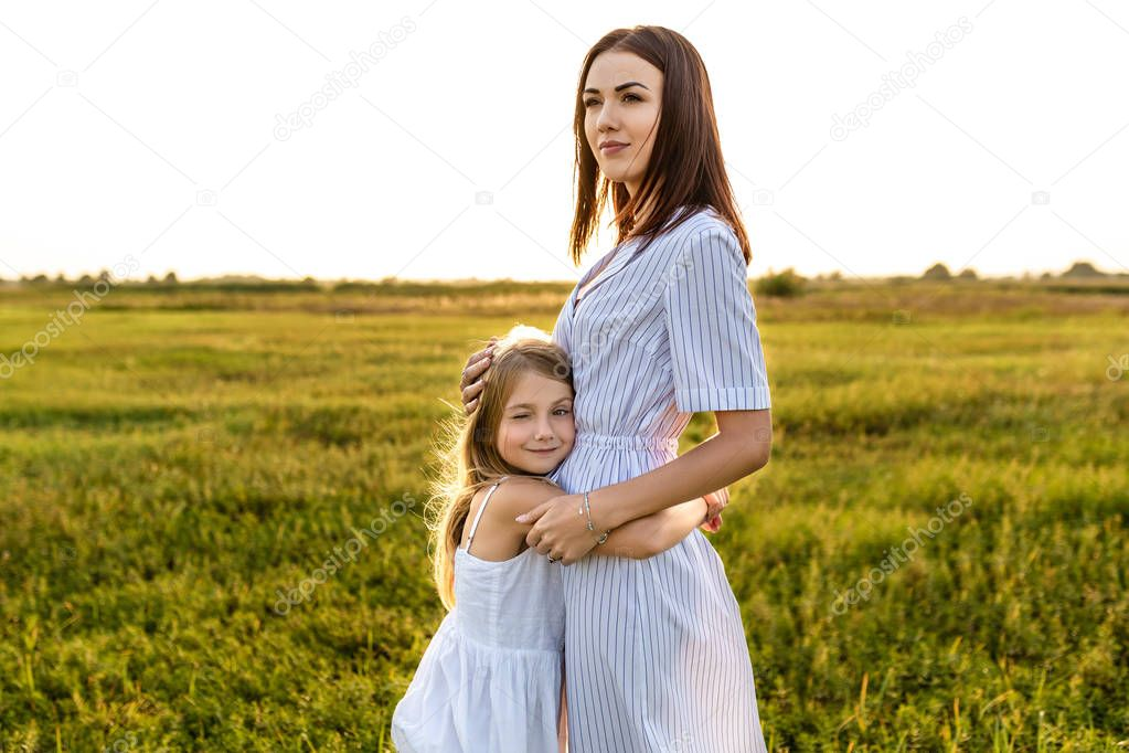 happy mother and daughter embracing in green field on sunset