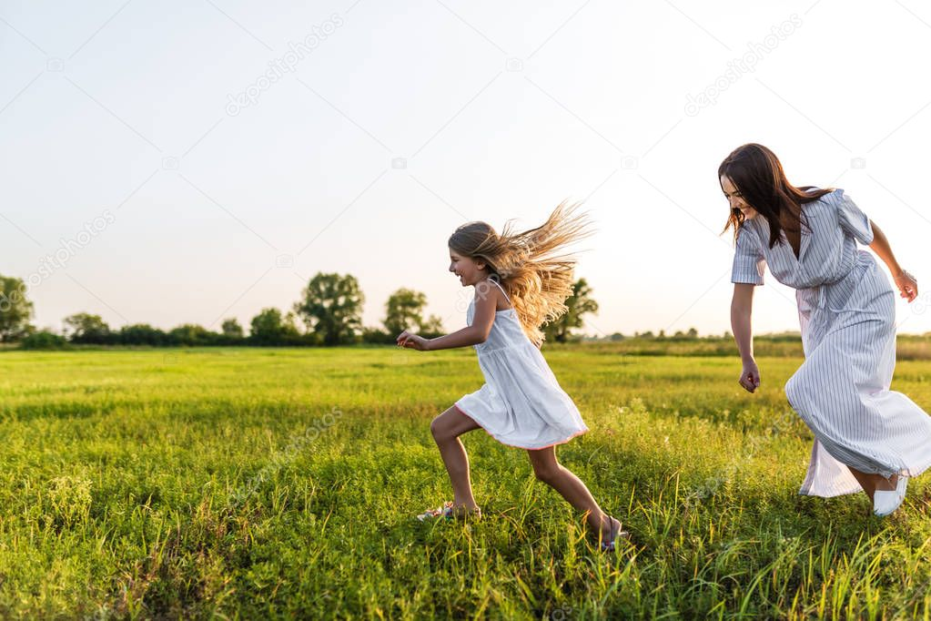 mother and daughter in white dresses running in green meadow