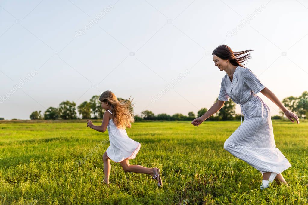 active mother and daughter in white dresses running in green meadow