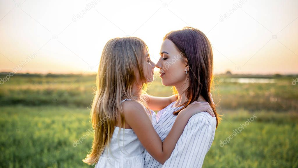 close-up portrait of mother and daughter embracing and touching noses in green field on sunset