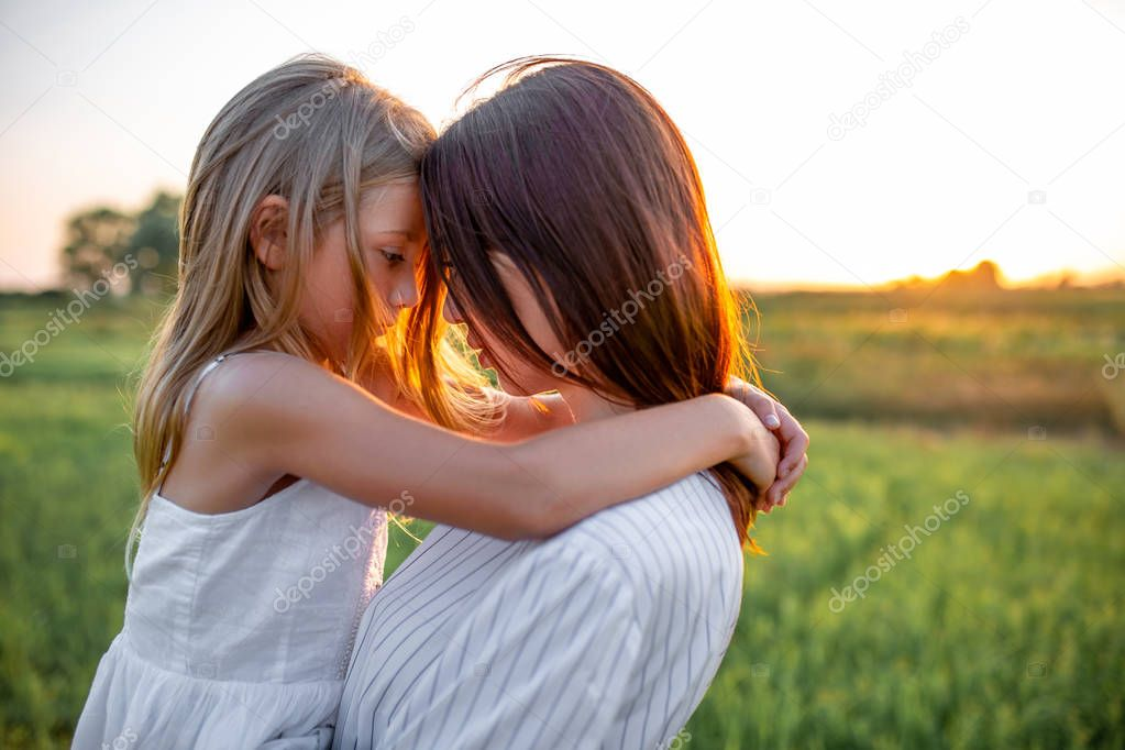 close-up portrait of mother and daughter embracing in green field on sunset