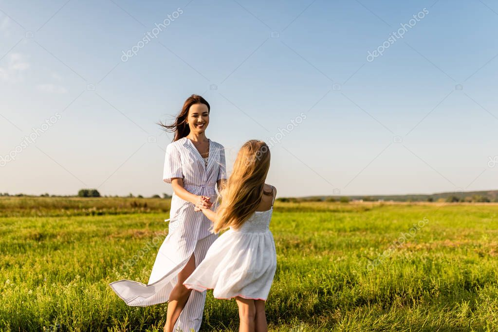 beautiful happy mother and daughter playing in green meadow