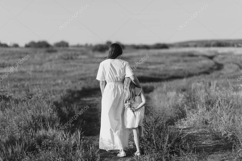 black and white shot of mother and daughter walking by rural road in green meadow