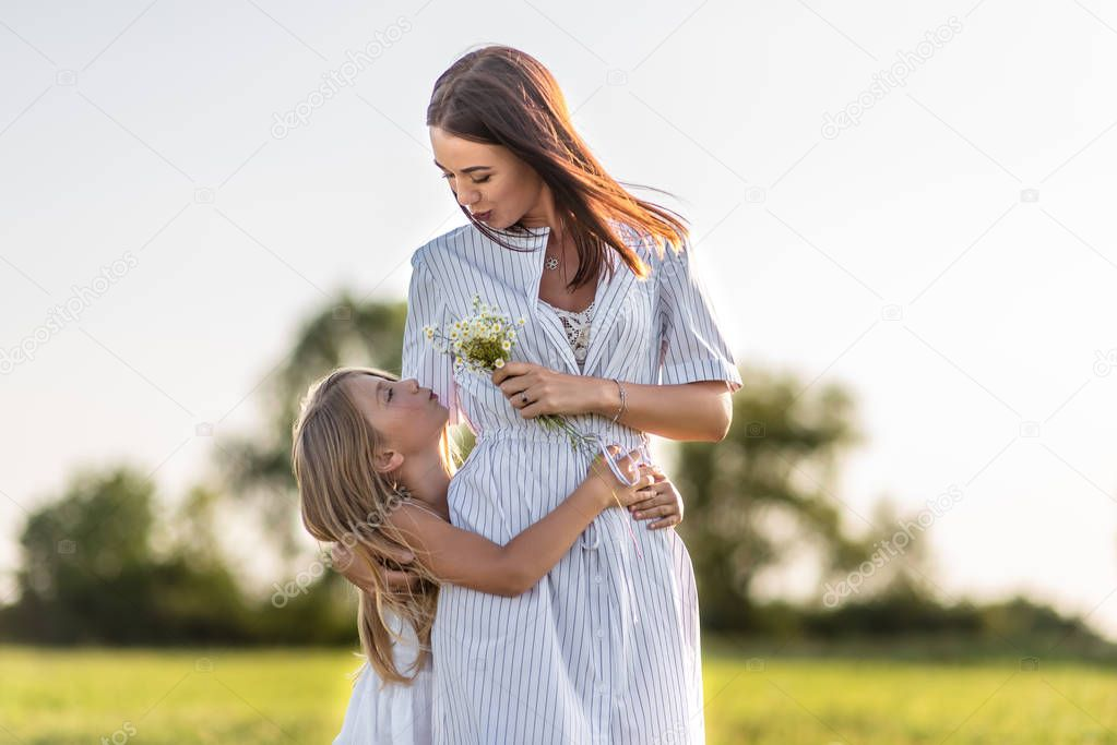 mother and daughter with field flowers bouquet embracing in green meadow