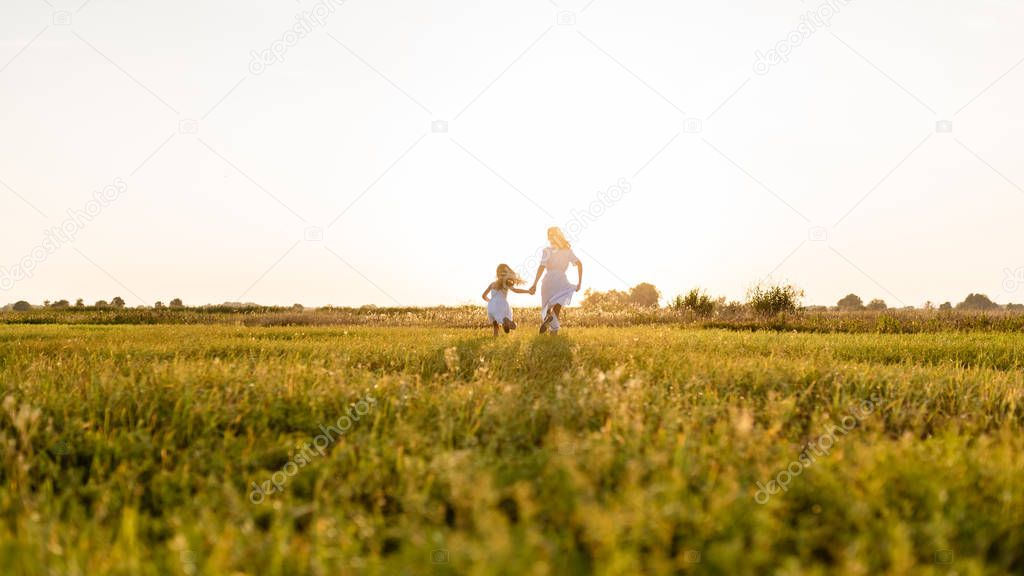 rear view of mother and daughter running in green meadow with sunset on background