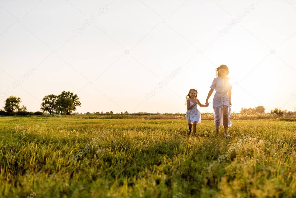 mother and daughter walking in green meadow with sunset on background