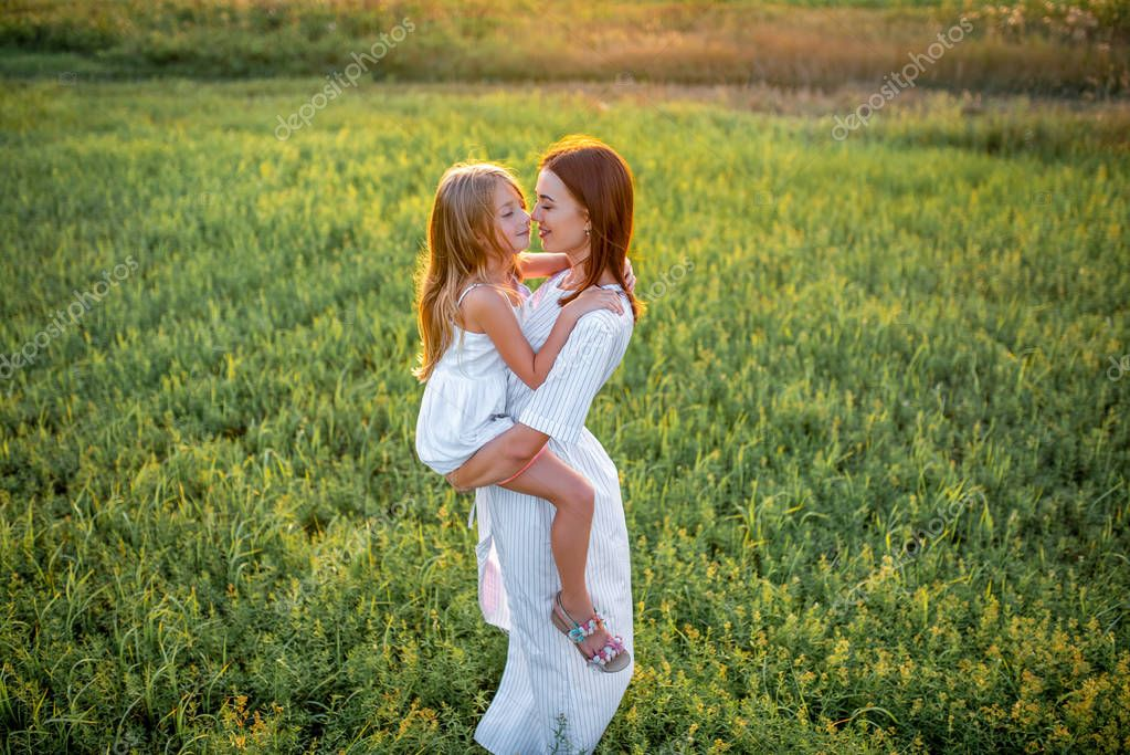 high angle view mother and daughter embracing in green meadow on sunset