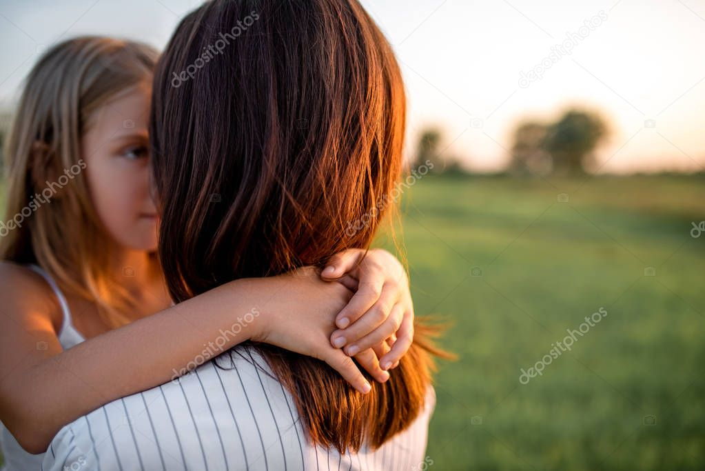 mother and daughter embracing in green meadow on sunset