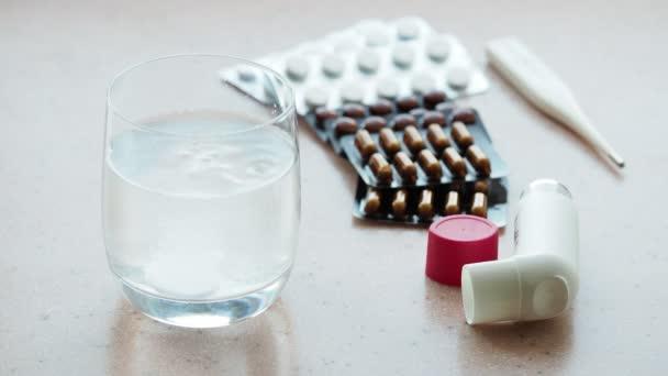 sklenice vody s šumivých tablet a různé pilulky na růžové kamenné desky