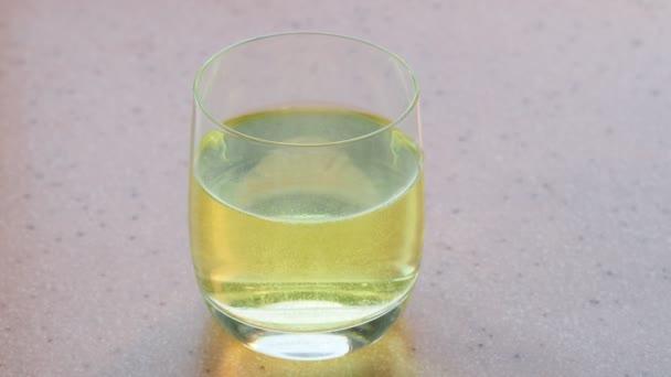 žlutá vitaminový ve sklenici vody na růžové kamenné desky