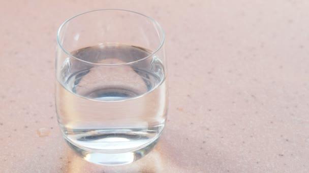 sklo čisté vody na růžové kamenné desky