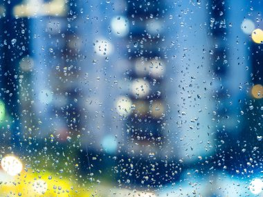 autumn rainy weather - view of blurred urban houses through the home window with raindrops in evening (focus on the rain drops on the glass)