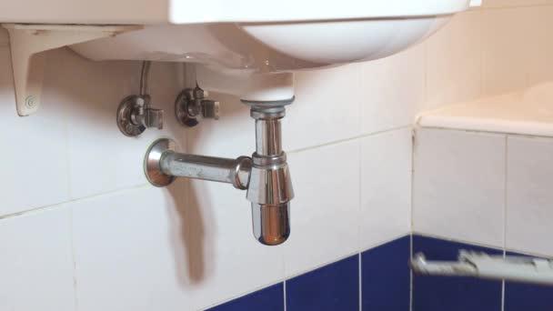 člověk opravuje malé klíč nastavitelný instalatér na sifon umyvadlo v koupelně