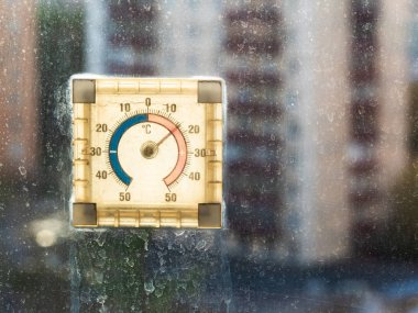 outdoor thermometer illuminated by sun on unwashed window at home shows the warm temperature on street