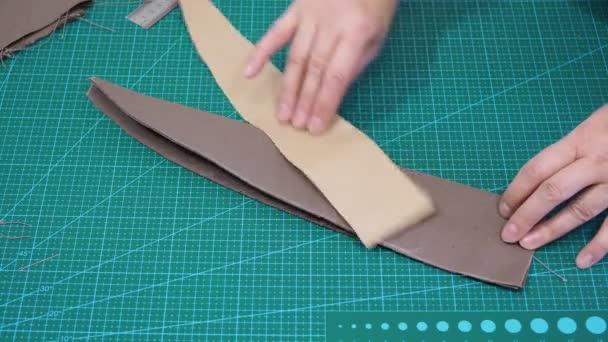 Werkstatt zur Herstellung von Textil- und Lederreisetaschen - Handwerker zeigt die ausgeschnittenen textilen Gegenstände einer Tasche