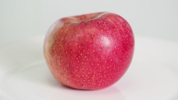úplně zralé červené jablko ovoce na bílé plotně se otočí na bílém pozadí