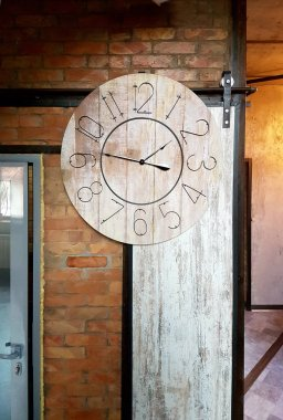 Large round clocks hang in the interior in a loft style
